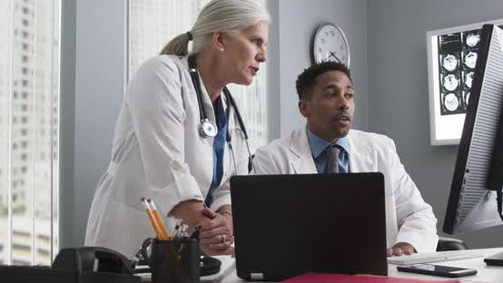Thumbnail for Two doctors working inside medical office looking at computer monitor and typing