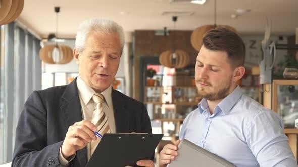 Thumbnail for Senior Businessman Explains Something on Clipboard To His Partner