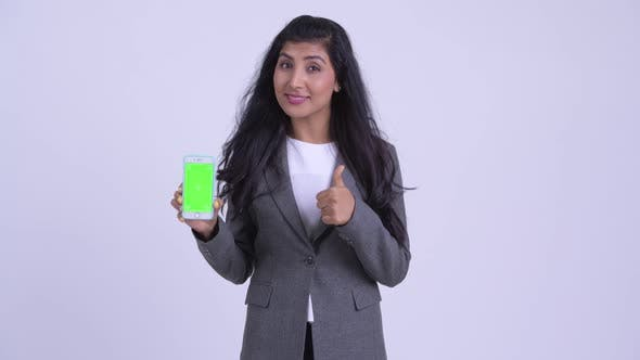 Young Happy Persian Businesswoman Showing Phone and Giving Thumbs Up