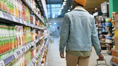Black Man Shopper in Jacket Wanders Along Long Grocery Shop