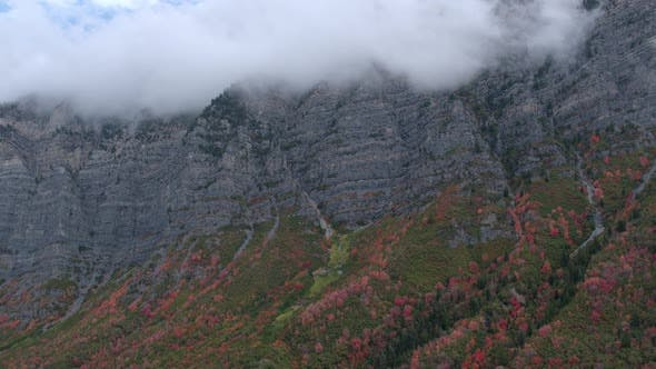 Thumbnail for Aerial view flying by a mountain with fall leaves and clouds