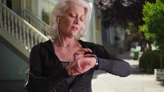 Mature woman in her 50s using smart watch checking pulse after jog outdoors