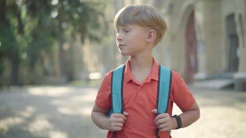 Portrait of Charming Little Boy Walking Along Schoolyard with Backpack. Blond Caucasian