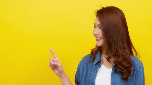 Young Asian lady smiling with with cheerful expression, shows something amazing at blank space