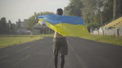 Confident Ukrainian Athlete Walking with National Flag Along Stadium and Turning To Camera. Portrait