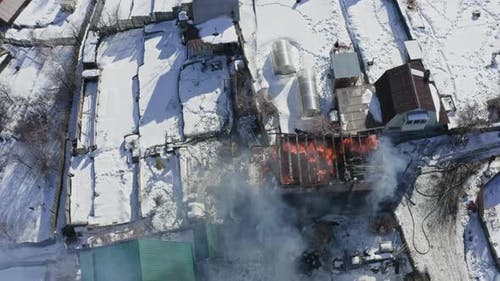 Top View of a House on Fire in a Village in Winter