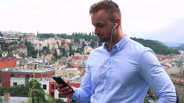 Cover Image for Young Handsome Business Man Listens Music with Earphone on Smartphone - City in Background