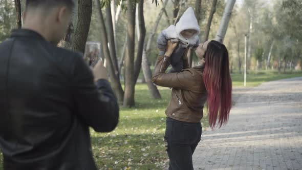 Thumbnail for Young Caucasian Man Taking Photos of Smiling Beautiful Woman Playing with Infant in Sunny Park