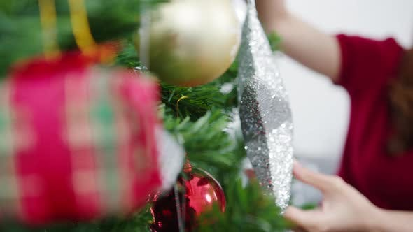 Asian female decorated with ornament on Christmas tree at Christmas and New Year festival.