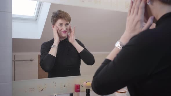 Thumbnail for Portrait of Cheerful Caucasian Senior Woman Looking at Her Reflection in Big Mirror, Smiling and