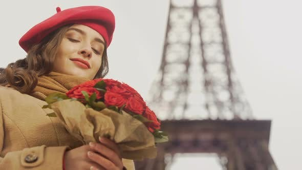 Thumbnail for Happy Beautiful Girl Admiring Bouquet Of Red Roses On Background Of Eiffel Tower