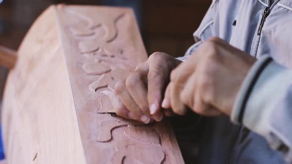 Cover Image for Artisan Processes the Wood of a Traditional Musical Instrument.