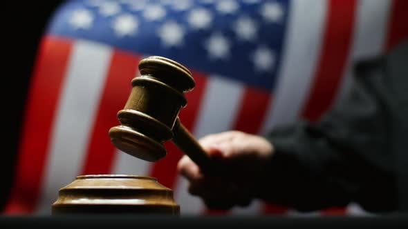 Thumbnail for Judge Hammering With Wooden Gavel in Hand Against Waving American Flag in United States Court