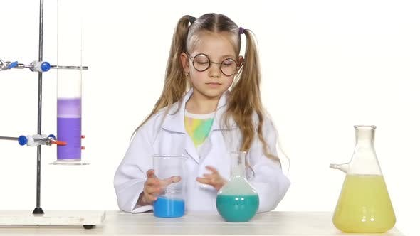 Thumbnail for Cute Girl with Ponytails in Uniform and Round Glasses Evaluates, Mixing, Standing By the Table