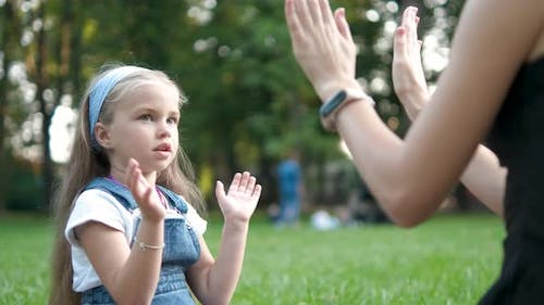 Pretty little child girl playing game with her mom with their hands outdoors in green summer park
