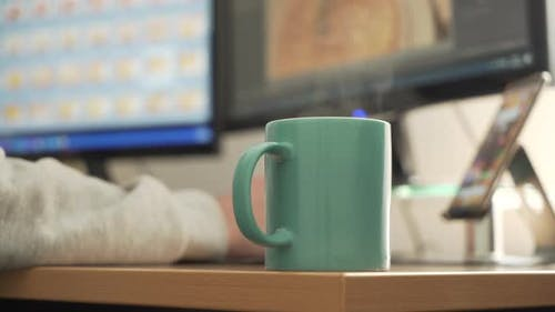 Photographer retouching photos, working at home with a cup of steaming coffee