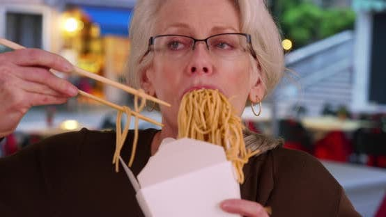 Thumbnail for Slow motion portrait of mature woman eating Chinese takeout