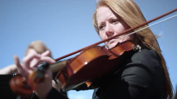Close up of a woman playing the Violin in an outdoor orchestra