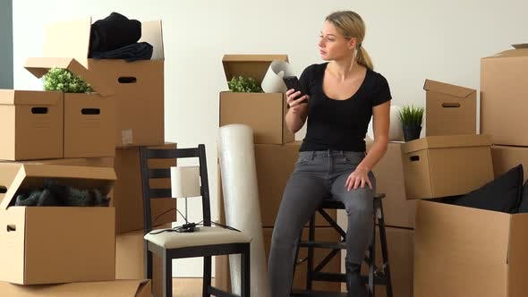 Thumbnail for A Moving Woman Sits on a Chair in an Empty Apartment and Takes Pictures of Cardboard Boxes