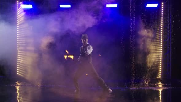 Fire Show in the Rain in the Studio. Professional Artist Performs a Variety of Fire Facilities