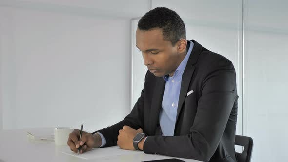 Thumbnail for Casual Afro-American Businessman Writing at Work Paperwork