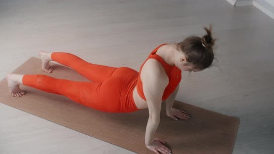 Attractive Young Woman Stretches Herself on the Floor on the Youga Mat, Yoga Classes in Slow Motion