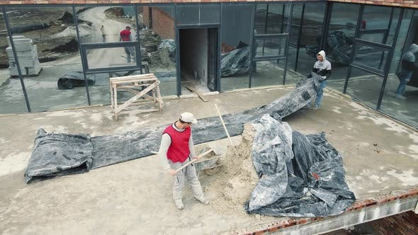 Male Builders Pour Sand Into the Cart