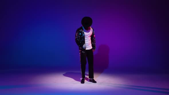 Cover Image for Young Stylish Man Dancing, Spotlight on a Blue Background