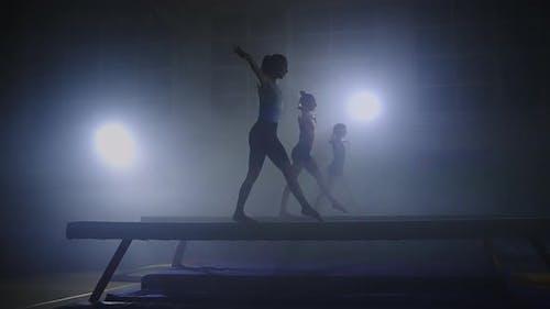Three Female Gymnasts is Performing Program on Balance Beam Synchronous Sport Team is Training