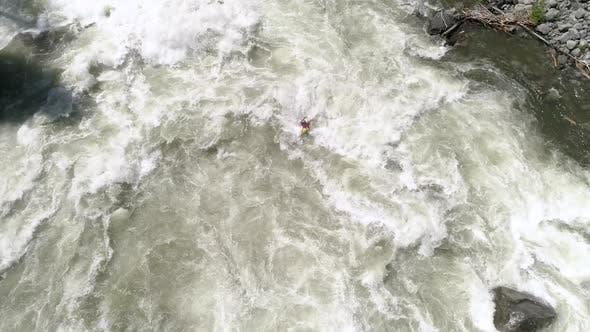 Thumbnail for Overhead Of Man Paddling Kayak On Raging White Water River Rapids In Spring Season