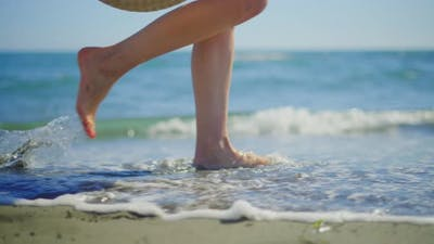 Woman legs being washed by ocean waves
