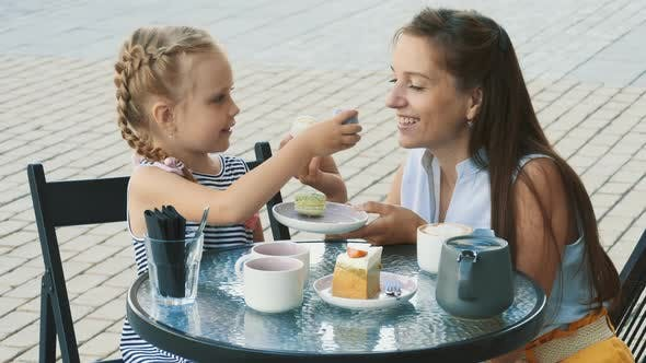 Thumbnail for Mother and her cute little daughter in outdoor cafe