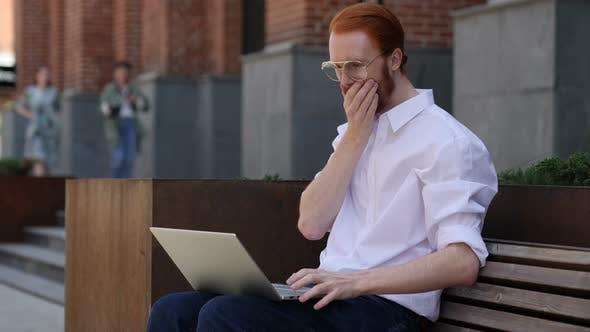 Astonished Designer Wondering while Using Laptop Sitting on Bench