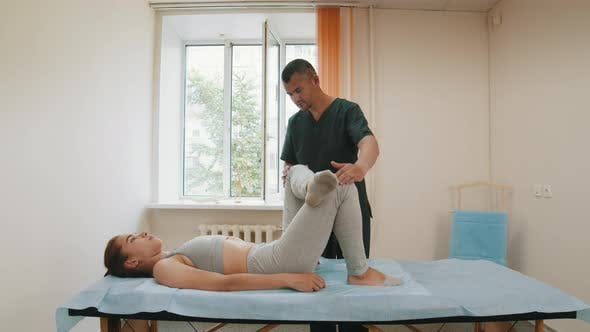Thumbnail for Woman Having an Osteopath Treatment - the Doctor Puts Her Leg on Another and Pushing To the Torso