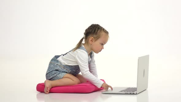 Thumbnail for Little Girl Is Sitting on Her Lap and Looking at the Laptop. White Background