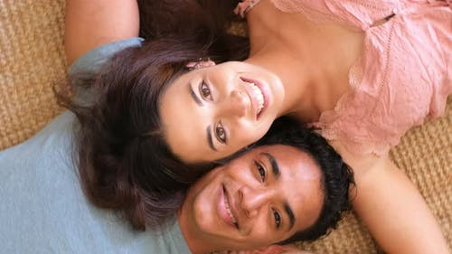 Happiness in relationship interracial young adult man and woman lay down on the floor at home