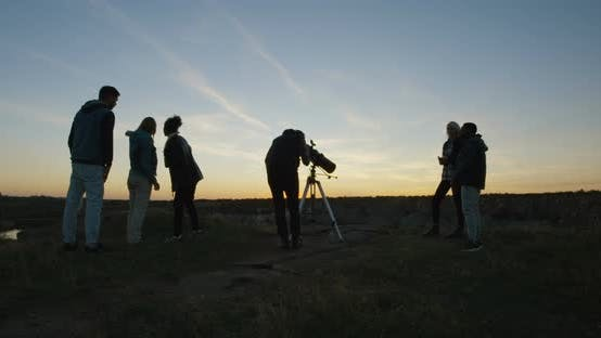 Thumbnail for Friends on Shore in Twilight Looking Through Telescope