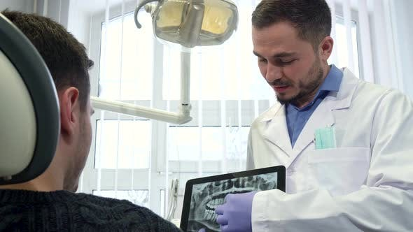 Thumbnail for Dentist Shows Male Client X-ray on His Tablet
