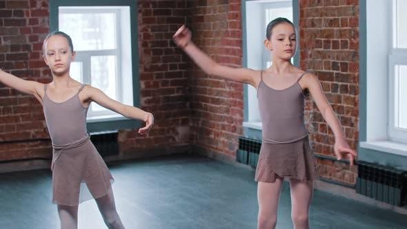 Two Ballerina Girls Train Synchronized Movements in the Studio