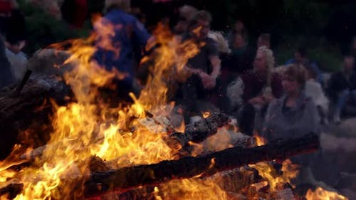 Flames Blazing from a Pile of Wood with People in the Background