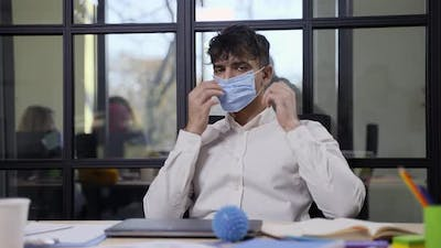 Serious Indian Male in Face Mask Posing in Office