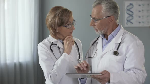 Cover Image for Male Doctor Showing Tablet to His Female Colleague Electronic Medical History
