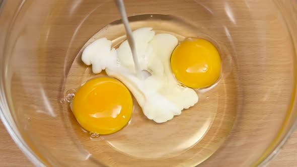Thumbnail for Milk Is Poured Into Plate with Eggs in Slow Motion