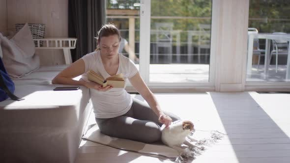 Thumbnail for Woman with Dog Reading Book in Living Room