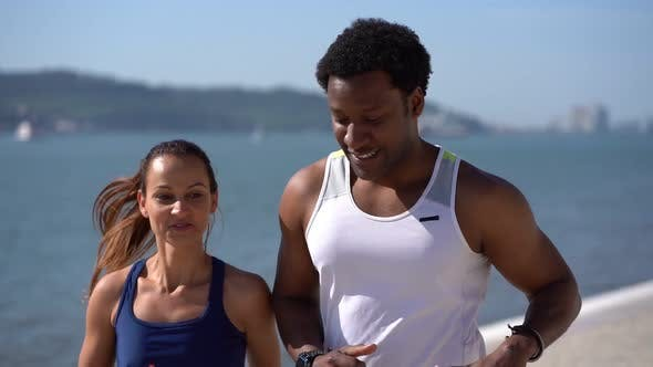Thumbnail for Multiethnic Couple in Sportswear Jogging Along Embankment