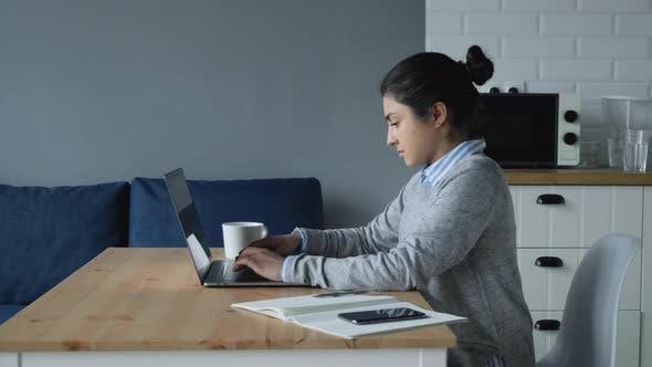 Thumbnail for Konzentrierte tausendjährige indische Frau, die am Computer Ta Home arbeitet.