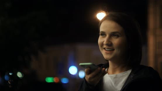 Girl Using Smart Phone Voice Recognition Dictates Thoughts Voice Dialing Message at Night Evening