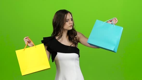 Thumbnail for Girl Keeps the Shopping Bags and Doubts What To Choose. Green Screen. Slow Motion
