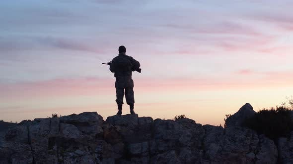 Soldier In The Morning Holds Guard With His Rifle