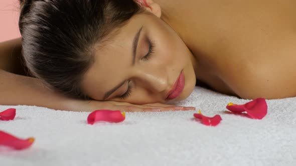Thumbnail for Girl Sleeps After Spa Treatments on Towels with Rose Petals